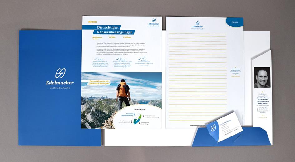 """Aufgeschlagene Infomappe von """"Edelmacher – wert(e)voll verkaufen"""" mit Visitenkarte und Modulblätter"""